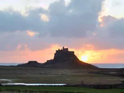 Sun rising behind Lindisfarne Castle on the Holy Island of Lindisfarne