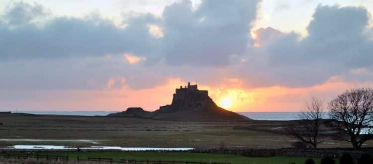 Sun rising behind Lindisfarne Castle on the Holy Island of Lindisfarne