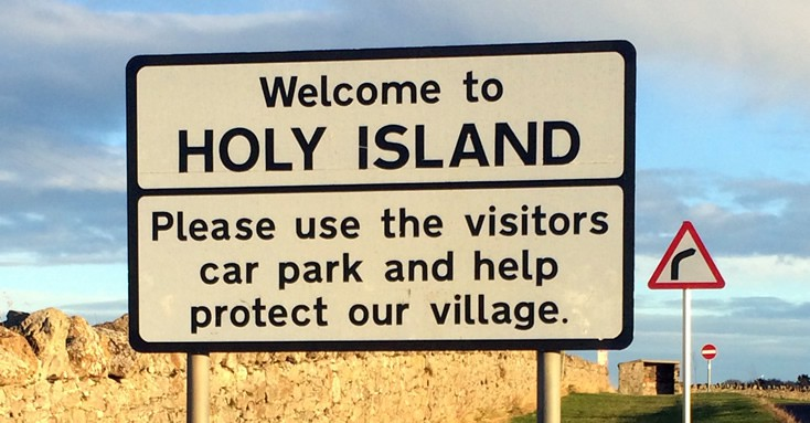 Sign saying: Welcome to Holy Island. Please use the visitors car park and help protect our village
