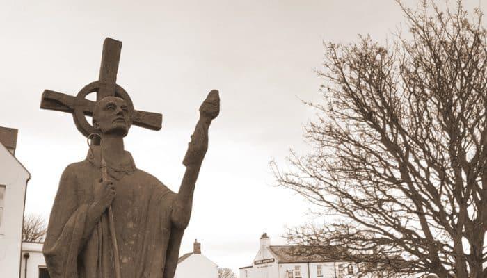 Statue of Saint Aidan of Lindisfarne next to Lindisfarne Priory ruins.